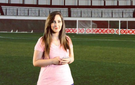 Young woman standing on empty soccer field