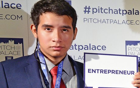 Young man holding a card that reads Entrepreneur