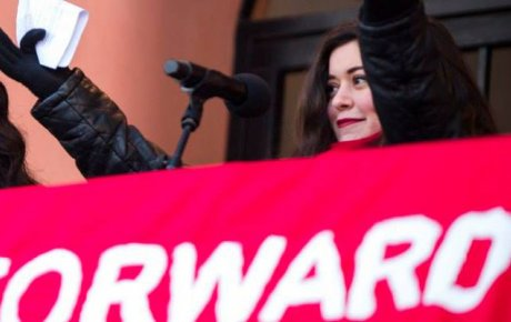 """Young woman holds arms stretched out in front of a microphone and sign with the word """"Forward"""""""