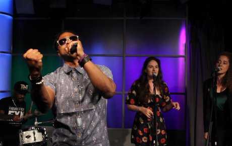 Man holding mic wearing sunglasses and holding his fist out as he sings on stage with background singers behind him