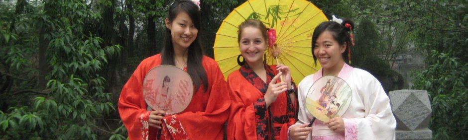 Group of women in kimonos holding up an umbrella and fans