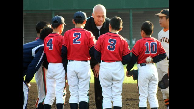 Cal Ripken gives baseball tips to young Japanese players.