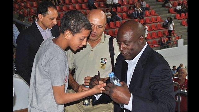 Sam Vincent signs his autograph on the palm of a Jordanian boy's hand.