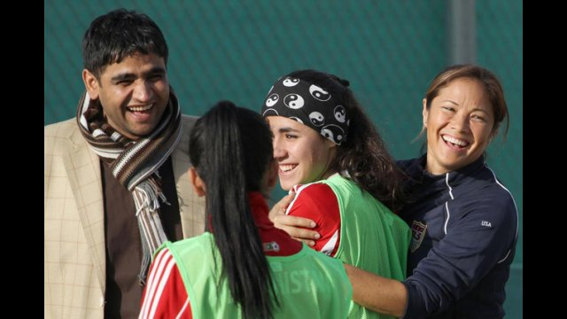 Sports Envoy Lorrie Fair embraces a member of the Afghan Women's National Soccer Team.