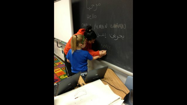 A participant in the volleyball coach program teaches a young girl how to write in Arabic during the group's visit to an elementary school in Tennessee.