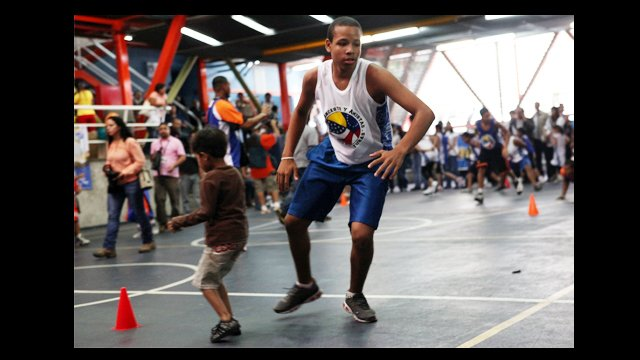 A clinic participant is joined on the court by a friend.