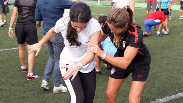 Young female athletes work to perfect the skills and drills that they learned from Julie Foudy during a soccer session.