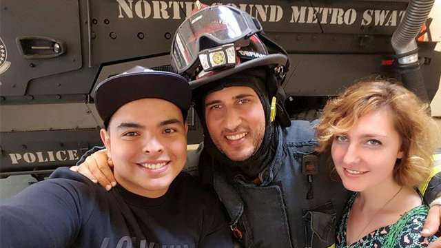 Two young people pose with a fire fighter