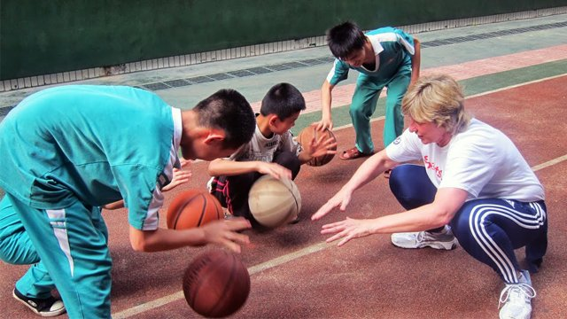 Dr. Clark teaches students basketball skills at Peiying Vocational School.