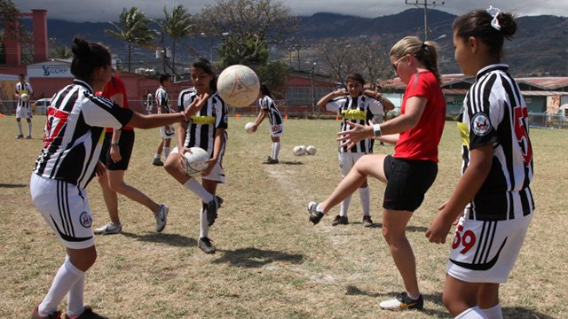 Amanda demonstrates her mastery of the soccer ball to the young soccer players.
