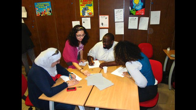 Syrian teachers work together on a project during a teacher training workshop.