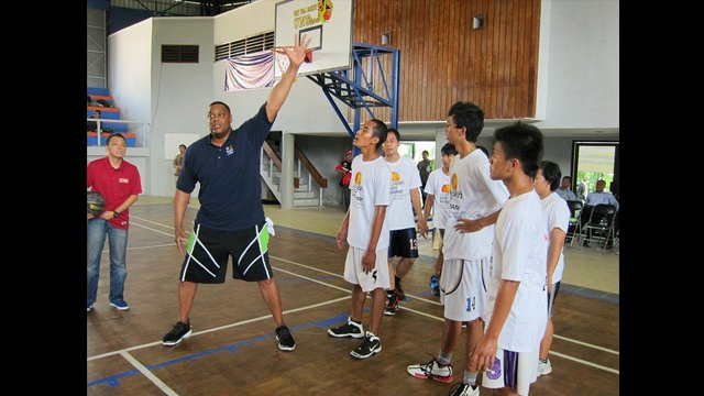 Rick Mahorn shares tips on defensive strategies with teenage boys during a basketball clinic in Indonesia.
