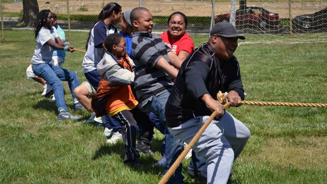 The group shows their strength and teamwork with the students of Paul Public Charter School during a tug of war activity.