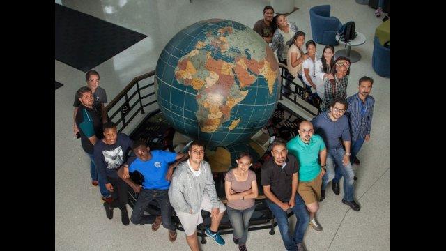 International students pose around a large globe statue