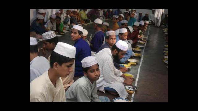 Young men gather in a madrassa for the evening meal called Iftar to break their fast durning the month of Ramadan. Kala Chandpur, Dhaka