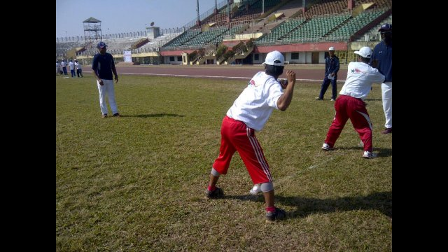 Young Indian athletes practice pitching with Joe Logan.