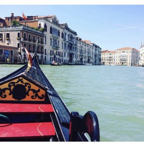 The front of a Gondola on a river pointing towards buildings