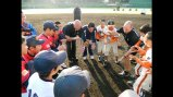 Cal Ripken huddles with young baseball players.