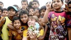 Filip posing with Bangladeshi children whle picking up garbage.