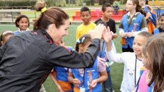 Julie Foudy provides positive encouragement to a girl for scoring a goal.