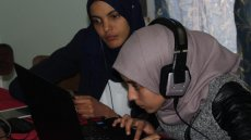 Two Algerian girls sit next to each other listening to headphones