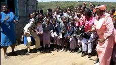 Maasai women and children greet American visitors.