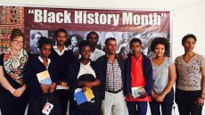 Group of people stand in front of Black History Month sign