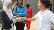 Women participant shaking hands with girl student during volunteer activity