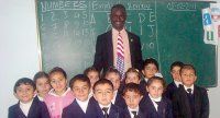 Male teacher wearing blue and red (USA colors) tie stands smiling with a group of young children in front of chalkboard