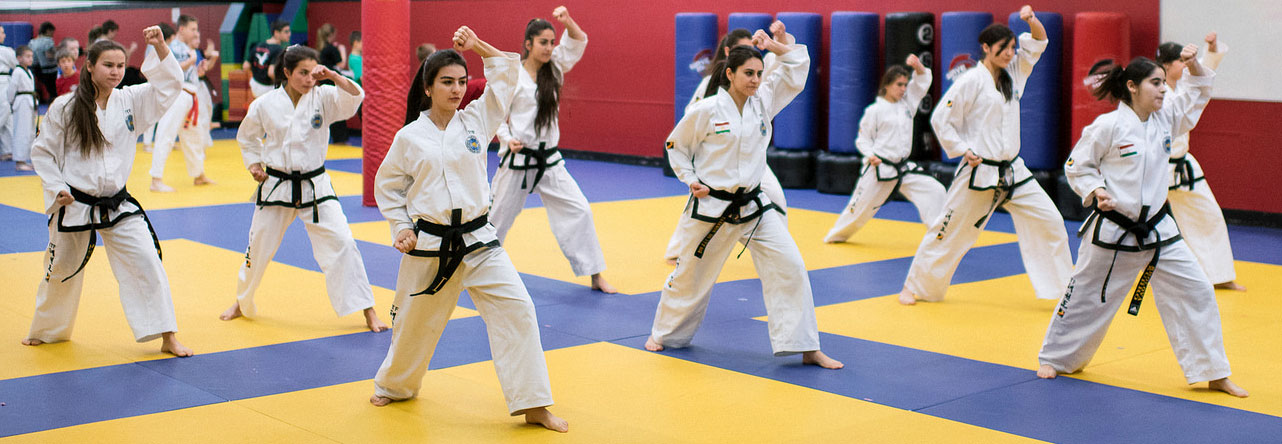 Group of girls in gym with karate uniforms on and standing in a blocking stance