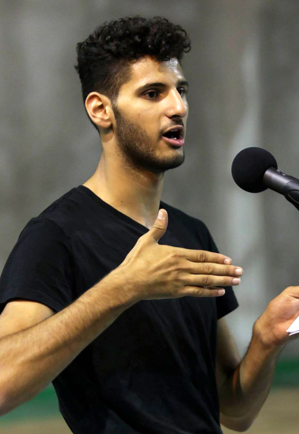 Young man stands in front of microphone talking