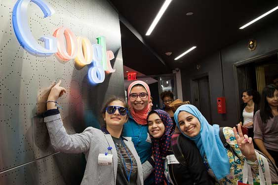 Girls posing in front of Google sign on the wall
