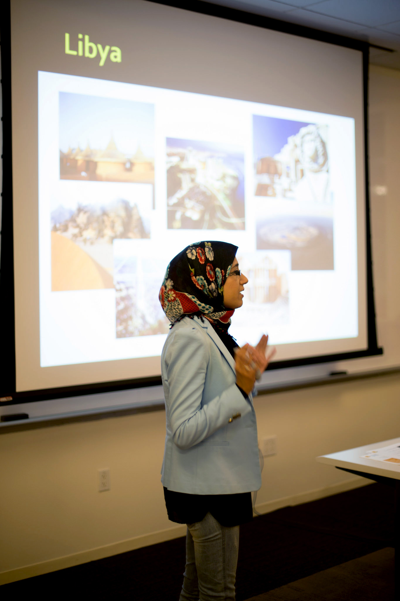 Woman standing in front of projection screen giving a presentation on Libya