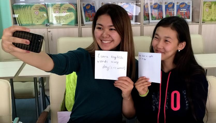 Girls taking a selfie with cell phone while holding up handwritten signs