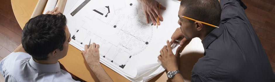 Architects sitting around a table looking at blueprints