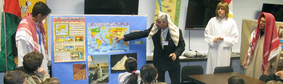 Photo of teacher in front of student pointing to a presentation board