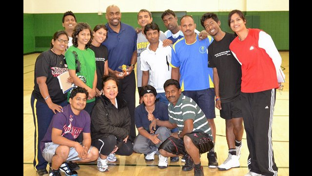 The group poses after a basketball session with Coach Joe Touomou, former Georgetown player.